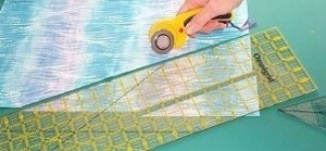 "Align the longer ruler with the freshly-cut edge.  Cut an angled strip, the desired width (3"" in this photo)."